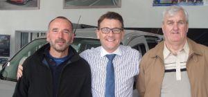 Dealer principle Tim Ward (centre) congratulates Paul King (left) and Chris Dibbin (right)
