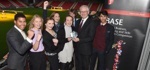 Head Judge Andrew McLaren presents the winners trophy to Milly Prendiville as their Mentor Richard J